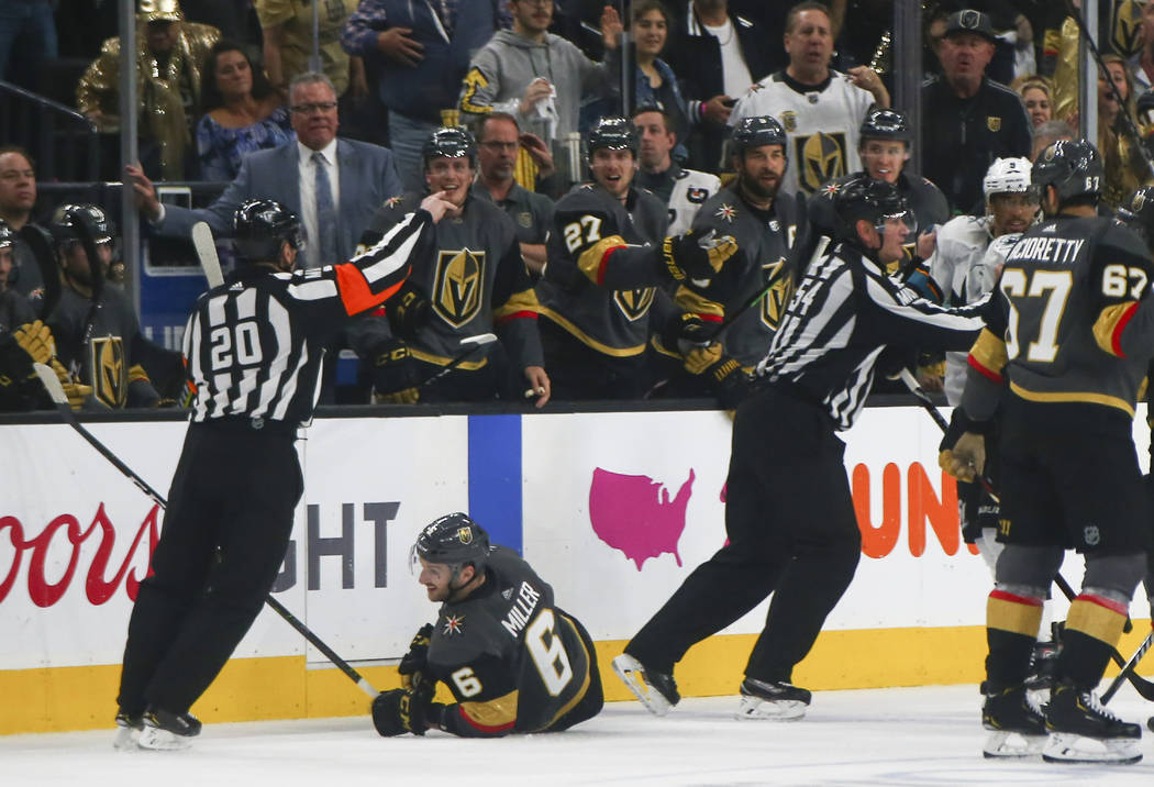 Golden Knights defenseman Colin Miller (6) is knocked to the ice by San Jose Sharks left wing E ...