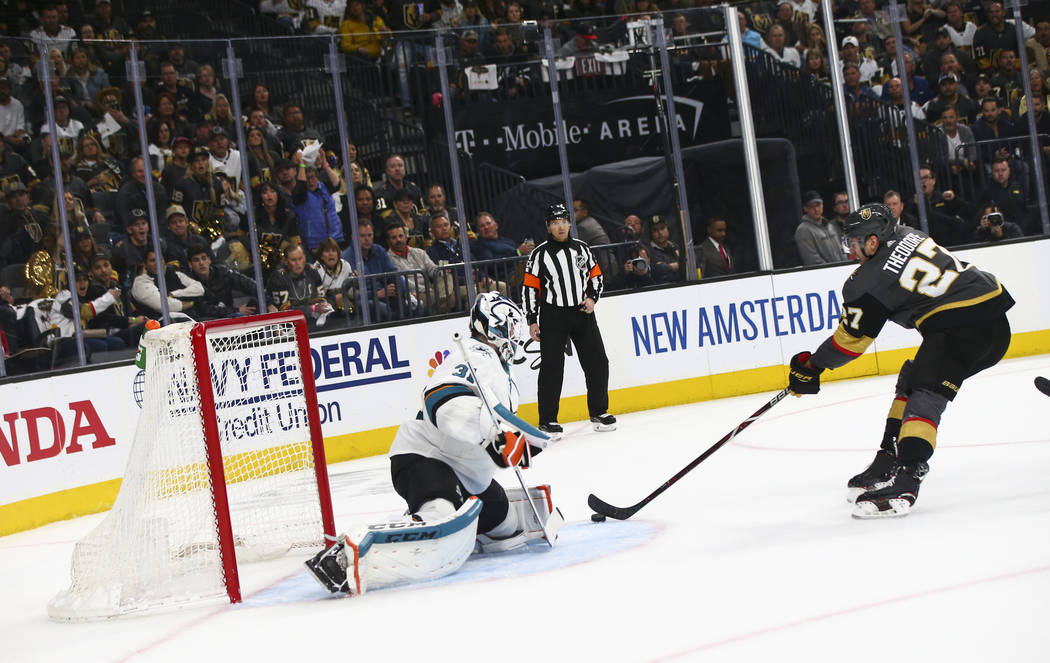 Golden Knights defenseman Shea Theodore (27) looks to score a goal past San Jose Sharks goalten ...
