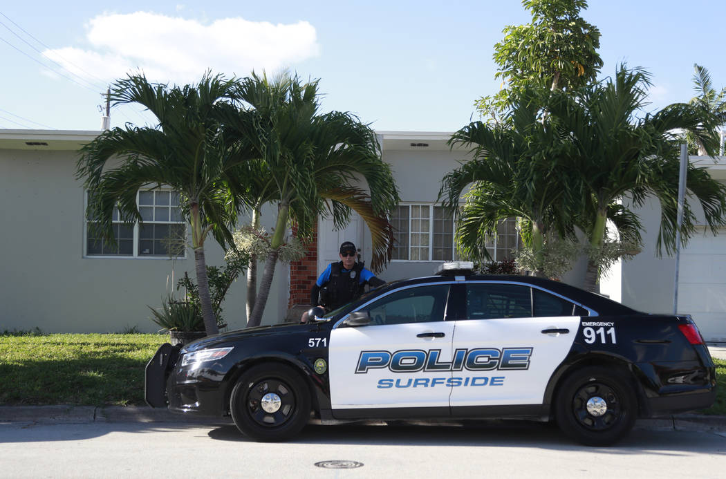 A town of Surfside, Fla., police officer stands guard in front of the home of Sol Pais, Wednesd ...