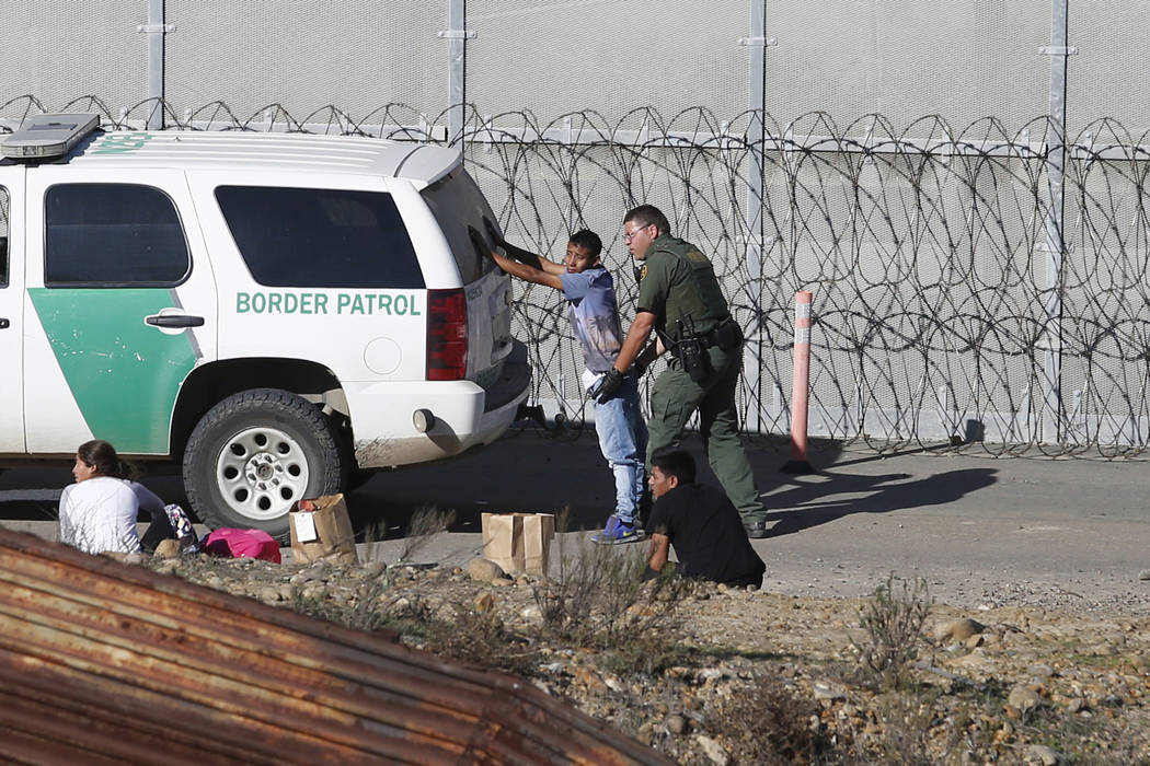Honduran asylum seekers are taken into custody Dec. 15, 2018, by U.S. Border Patrol agents afte ...