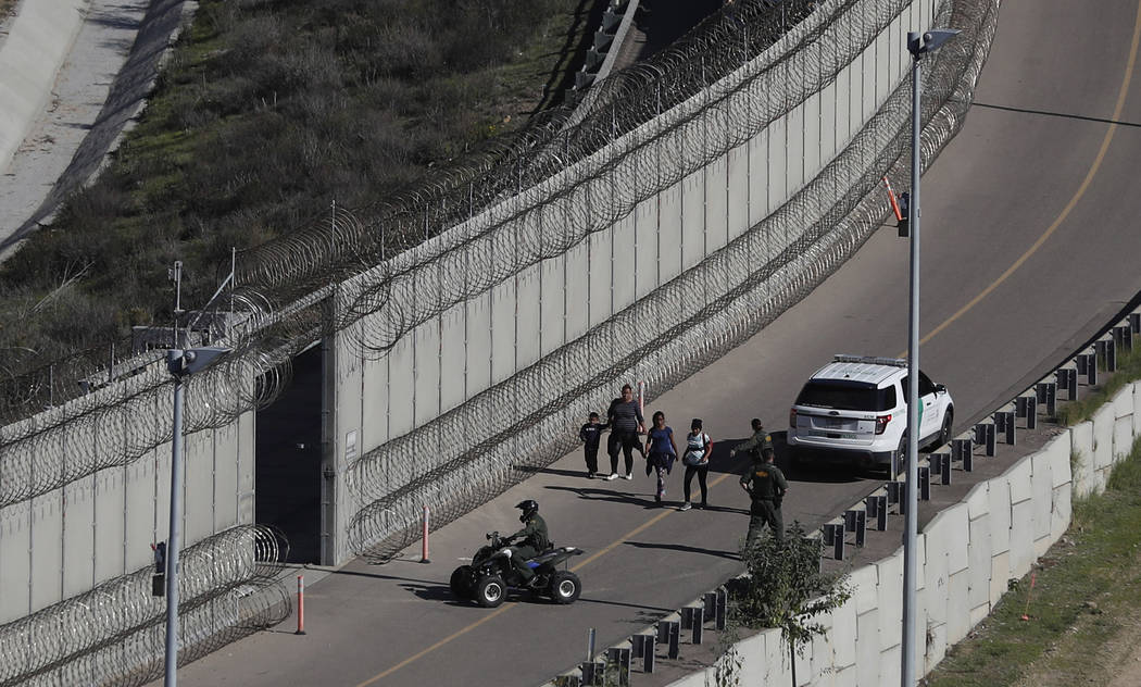 FHonduran asylum seekers are taken into custody by U.S. Border Patrol agents on Dec. 16, 2018, ...