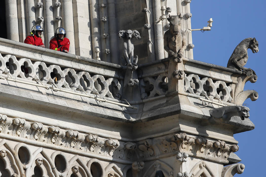 Firefighters wait at a balcony of Notre Dame cathedral Wednesday, April 17, 2019 in Paris. Near ...