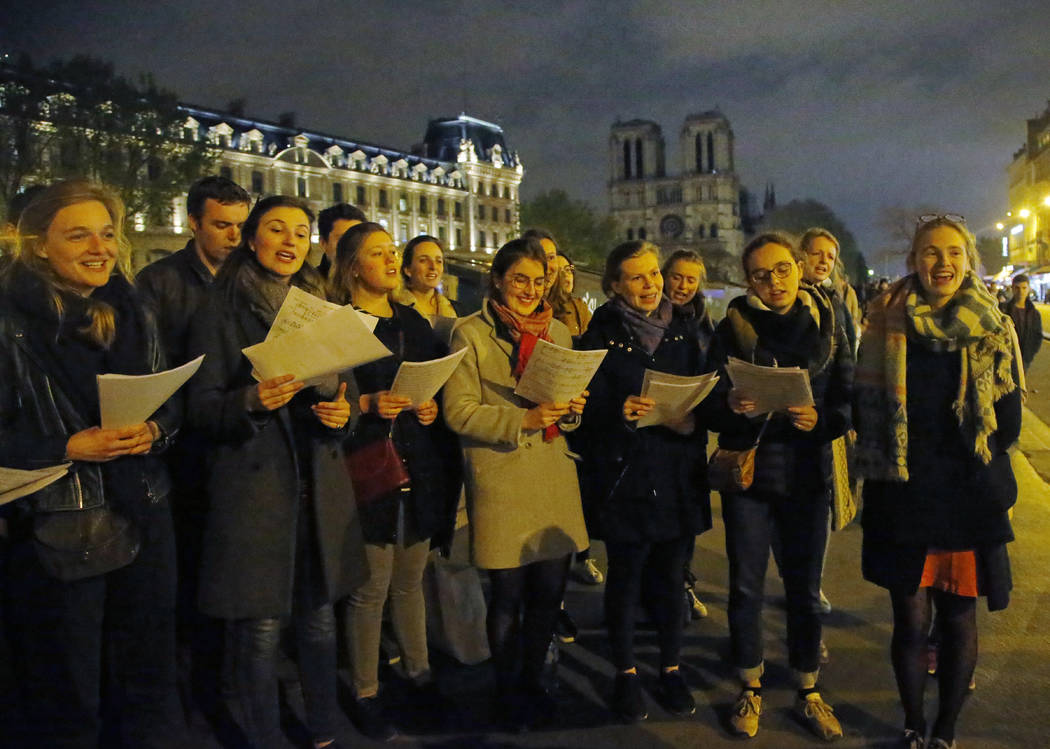 People attend a vigil in Paris, Tuesday April 16, 2019. Firefighters declared success Tuesday i ...