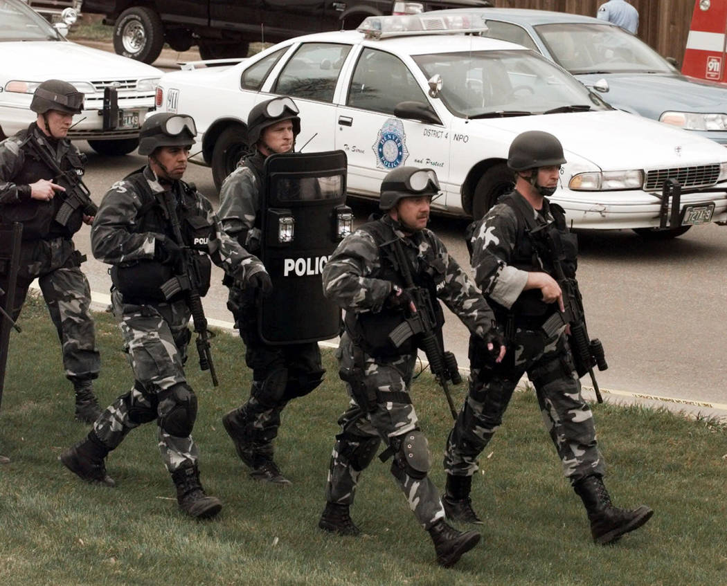 Members of a police SWAT team march to Columbine High School in Littleton, Colo., on April 20, ...