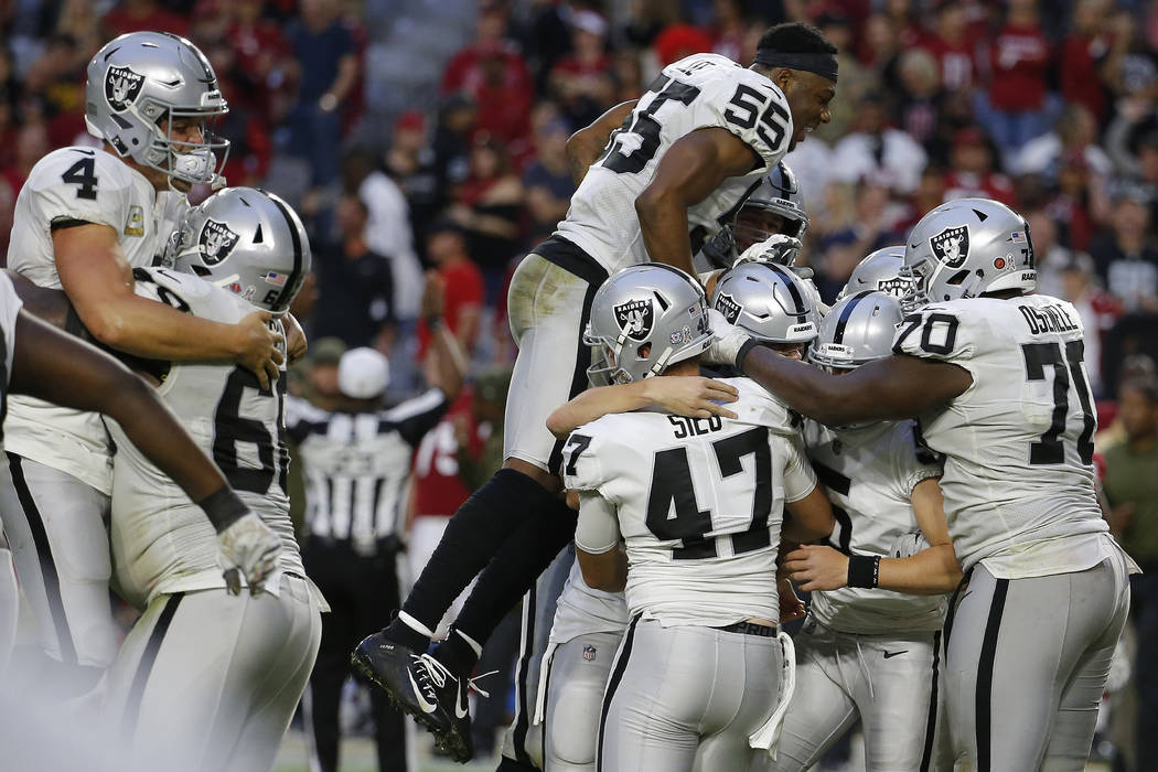 The Oakland Raiders celebrate as time expires during the second half of an NFL football game ag ...