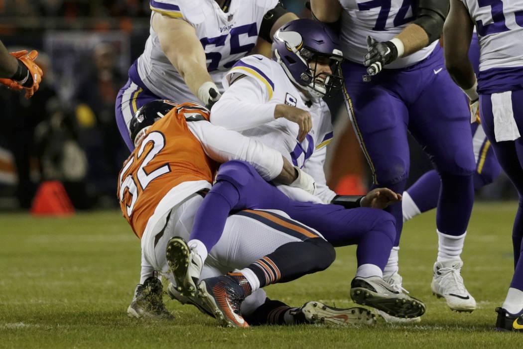 Minnesota Vikings quarterback Kirk Cousins (8) is tackled by Chicago Bears outside linebacker K ...