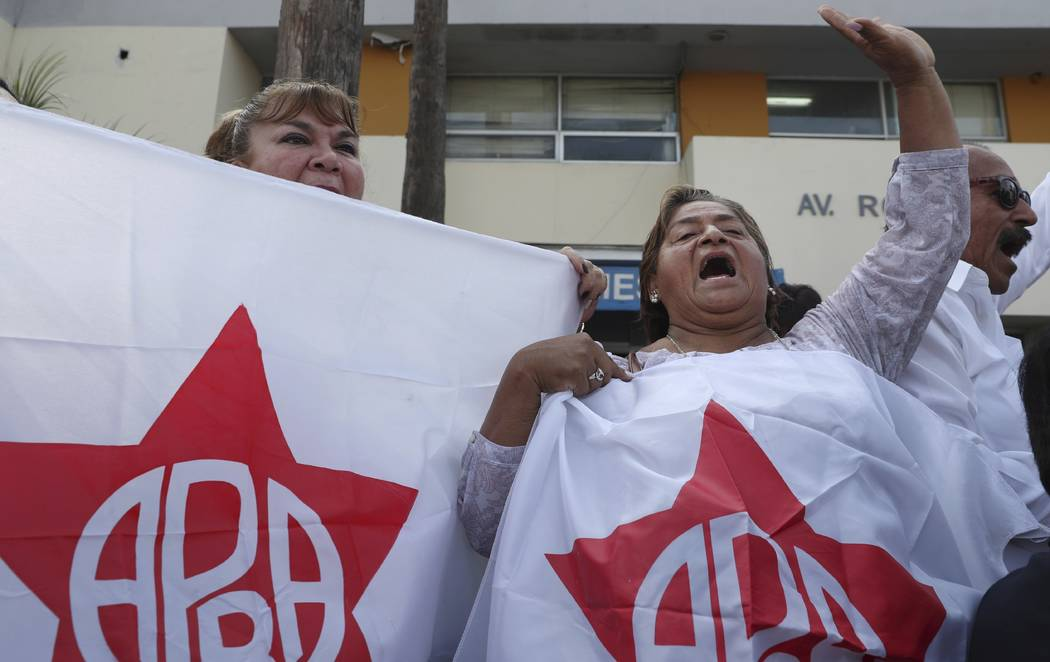 Supporters of former Peruvian President Alan Garcia gather outside the hospital where Garcia wa ...