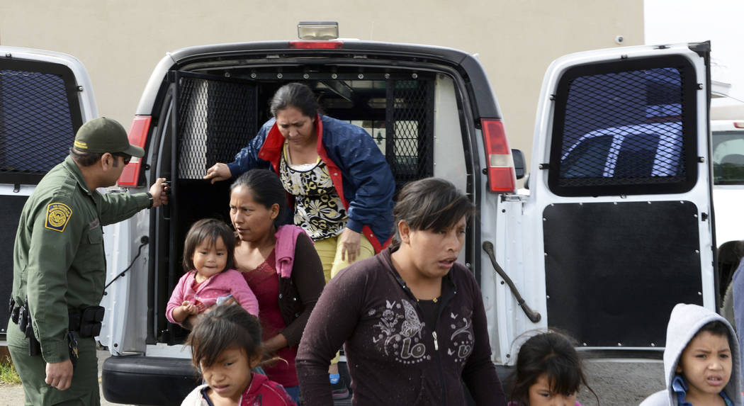 In this Friday, April 12, 2019 photo, a U.S. Border Patrol agent helps migrants out of a van at ...