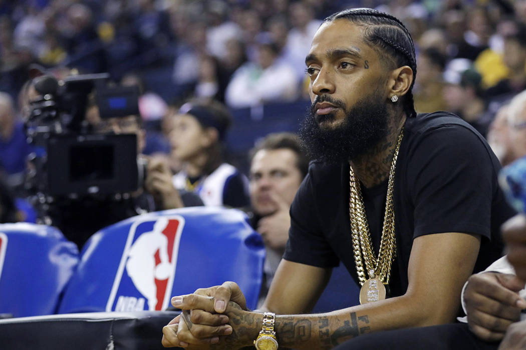 Rapper Nipsey Hussle watches an NBA basketball game between Golden State and Milwaukee in Oakla ...