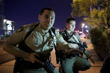 Police officers advise people to take cover near the scene Oct. 1, 2017, of a shooting near the ...