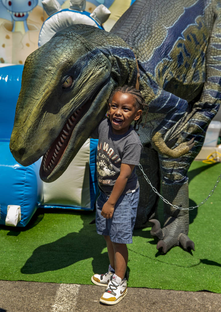 R.J. Jefferson, 4, is pleased to be meeting Blew the Dinosaur in the Event By Catalina booth as ...