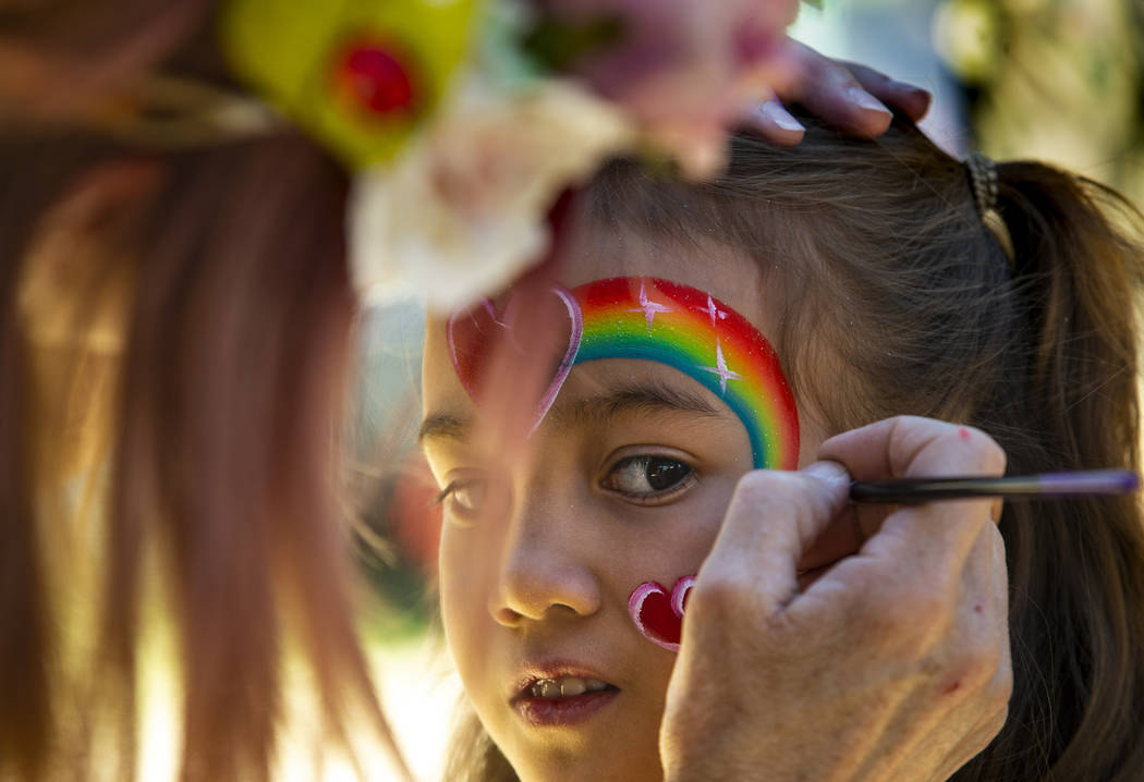 Alana Cano, 9, has a rainbow design painted on her face by Pamm Sundlie with Magic Wand Face Pa ...