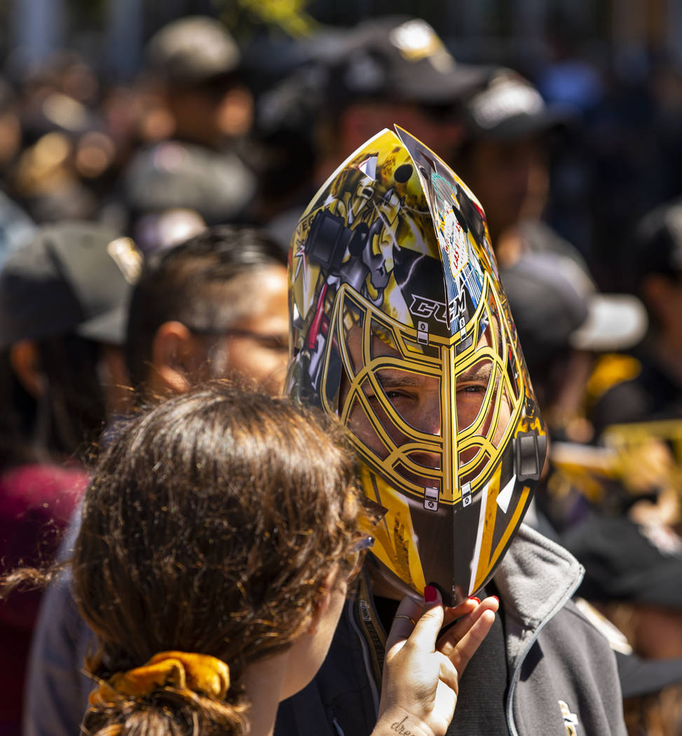 A fan wears a cardboard mask as he and others send off the Golden Knights players departing Cit ...