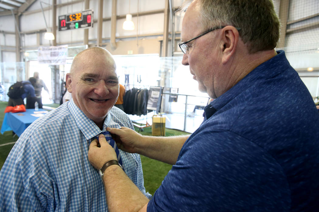 U.S. Marine Corps veteran Michael Mosley, 61, gets help with his tie from photographer Mikel Co ...