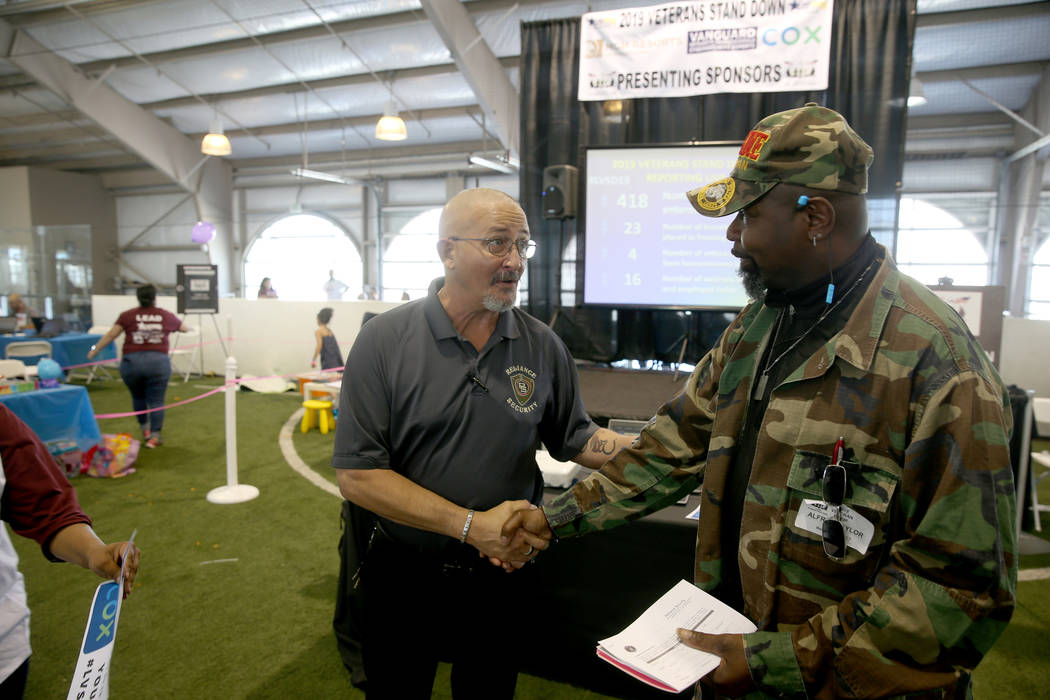 Ronald Gibson of Reliance Security, left, sets up a job interview with U.S. Marine veteran Alfr ...