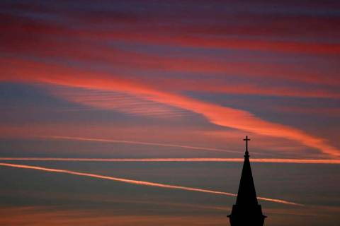Contrails from jets glow pink as they are illuminated by the setting sun in the skies beyond a ...