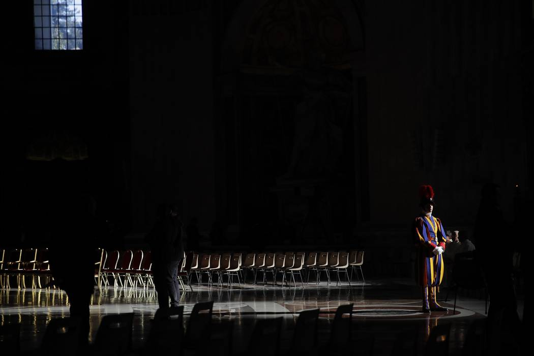 A Swiss Guard stands attention prior to a Holy Thursday Mass with blessing of oils, in St. Pete ...