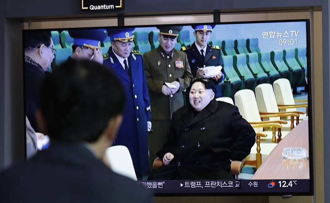 """A man watches a TV news program reporting about North Korea's test-fire of a """"new-type tac ..."""