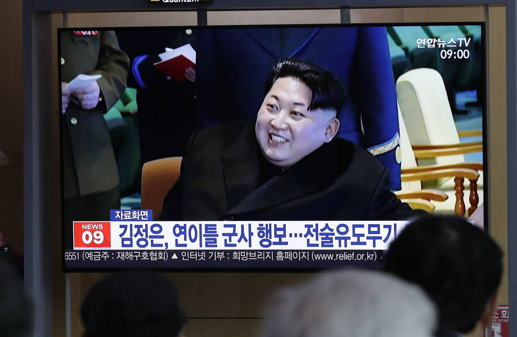 """People watch a TV news program reporting about North Korea's test-fire of a """"new-type tact ..."""