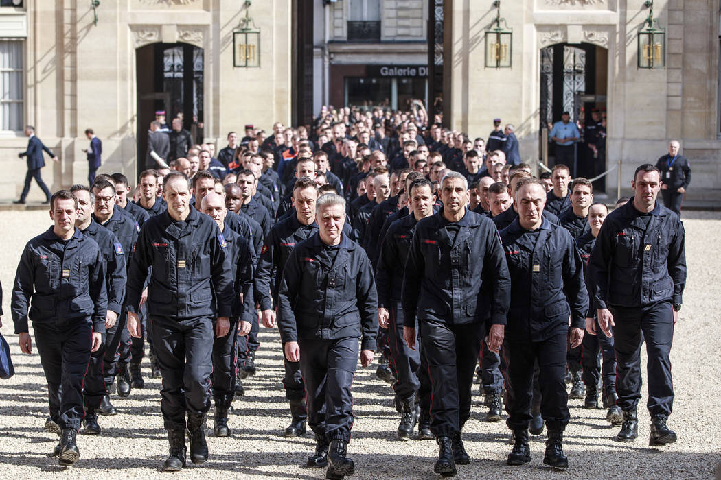 Firefighters and security forces who took part to the fire extinguishing operations at Notre Da ...