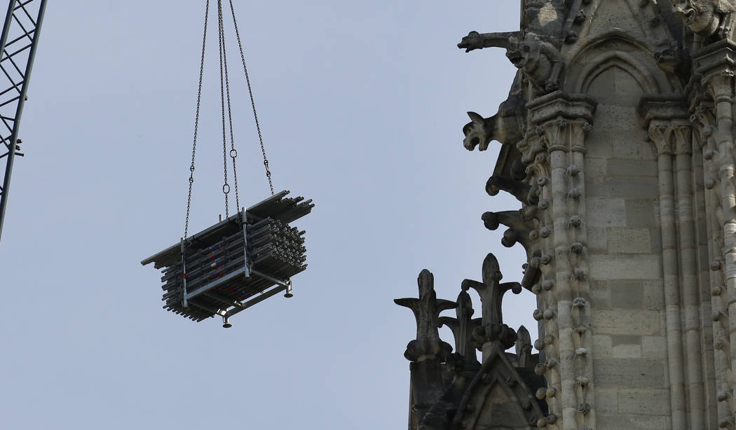 A crane hoists scaffolding past gargoyles outside the Notre Dame Cathedral in Paris, Thursday, ...