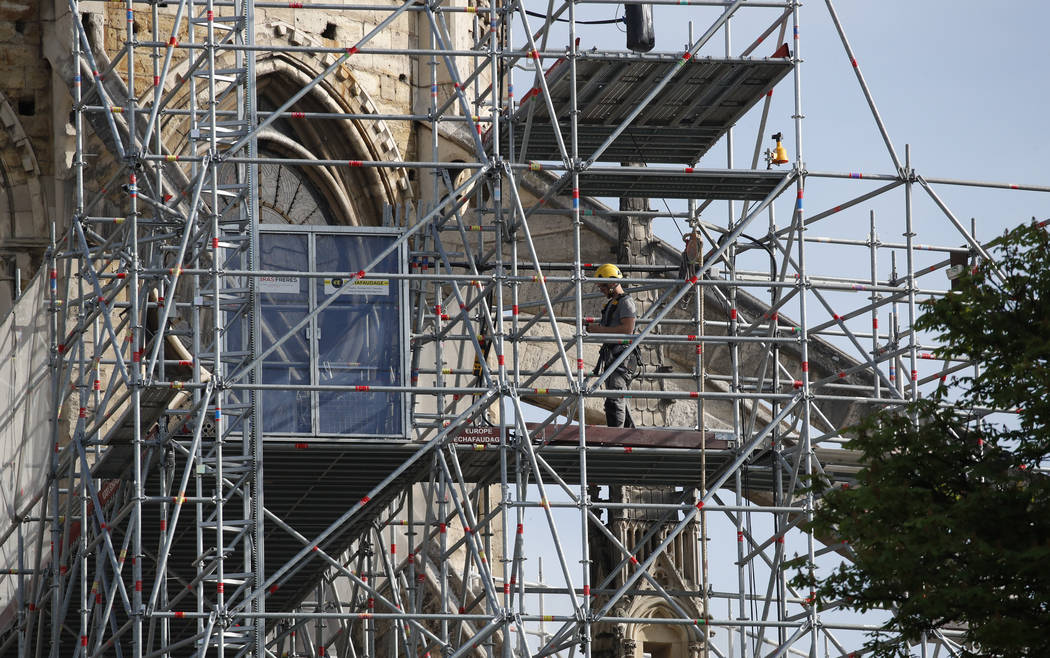 A man works on the scaffolding on the facade of the Notre Dame Cathedral in Paris, Thursday, Ap ...