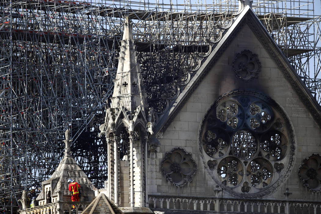 A firefighter makes his way on a balcony of Notre Dame Cathedral Wednesday, April 17, 2019 in P ...