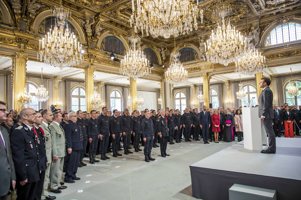 French President Emmanuel Macron stands at attention after addressing Paris Firefighters' briga ...