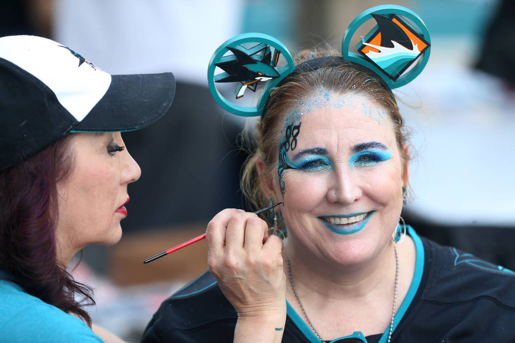 Celeste Oda, left, paints the face of Christie Wendeling, before Game 5 of an NHL Western Confe ...