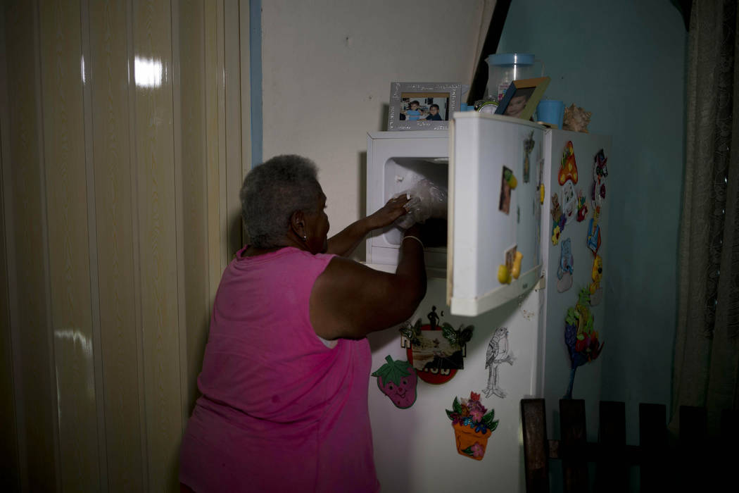 Pura Castell puts in her freezer the three pieces of chicken she received from a government-run ...