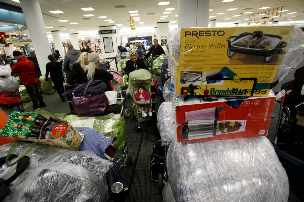 FILE - In this Dec. 16, 2010 FILE photo, carts are loaded with luggage as passengers wait in li ...