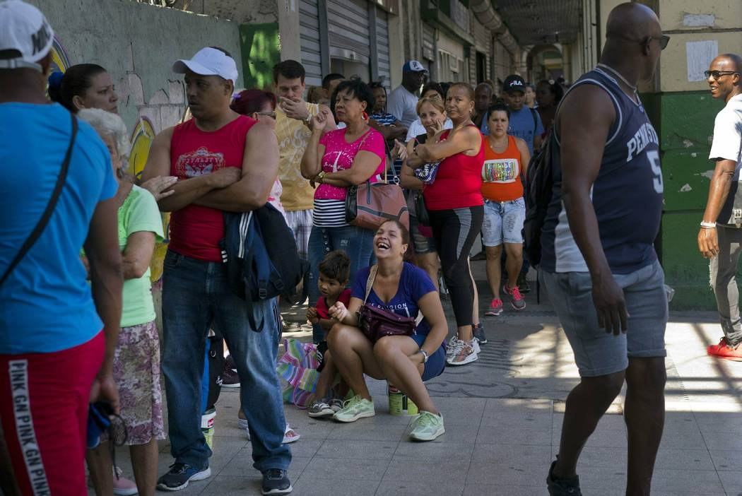 People wait in line to buy chicken at a government-run grocery store in Havana, Cuba, Wednesday ...