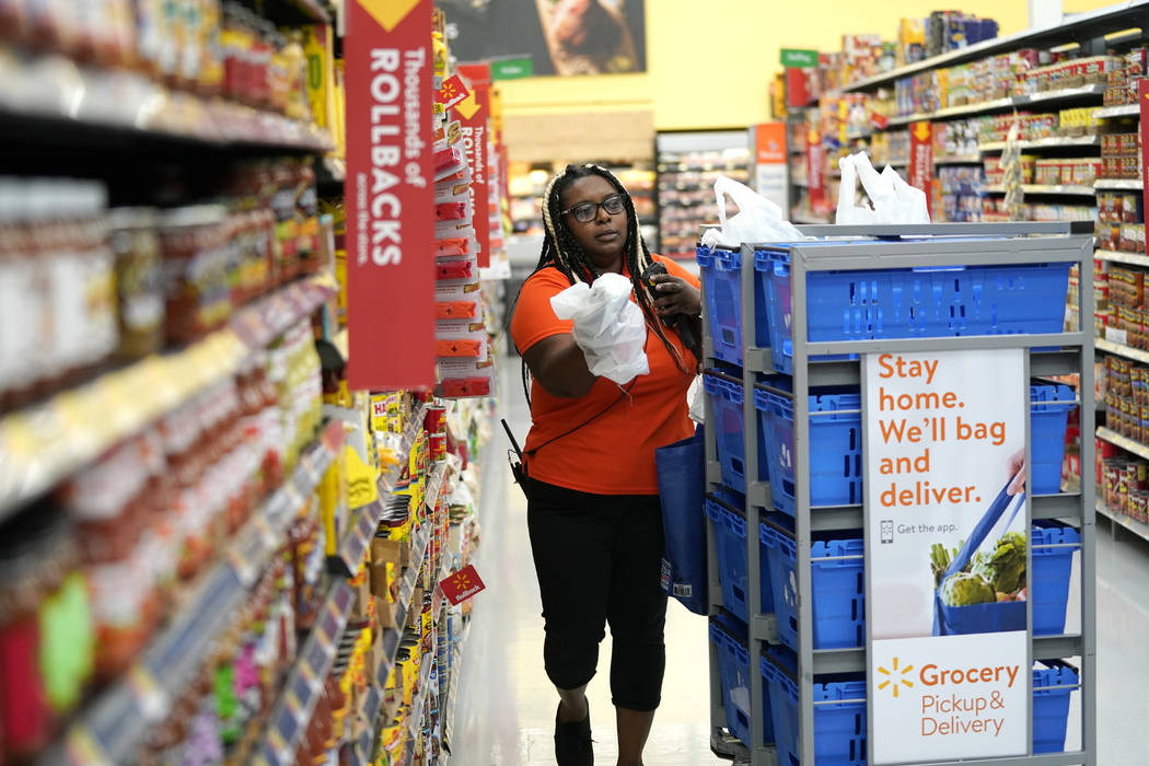 In this Nov. 9, 2018, file photo, Walmart associate Alicia Carter fulfills online grocery order ...