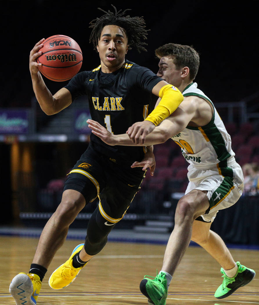 Clark's Frankie Collins (1) runs with the ball while being guarded by Bishop Manogue's Cort Bal ...