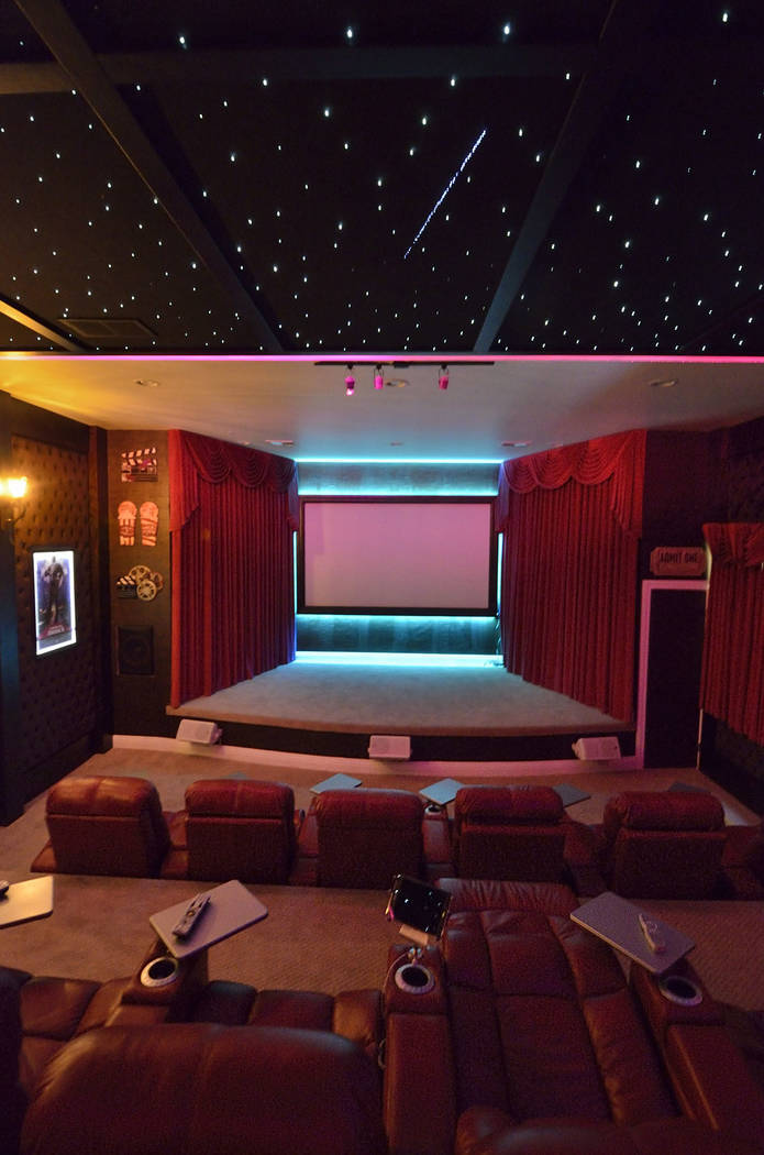 The theater walls are red velvet-tufted fabric, and one wall features faux leather paper. LED l ...