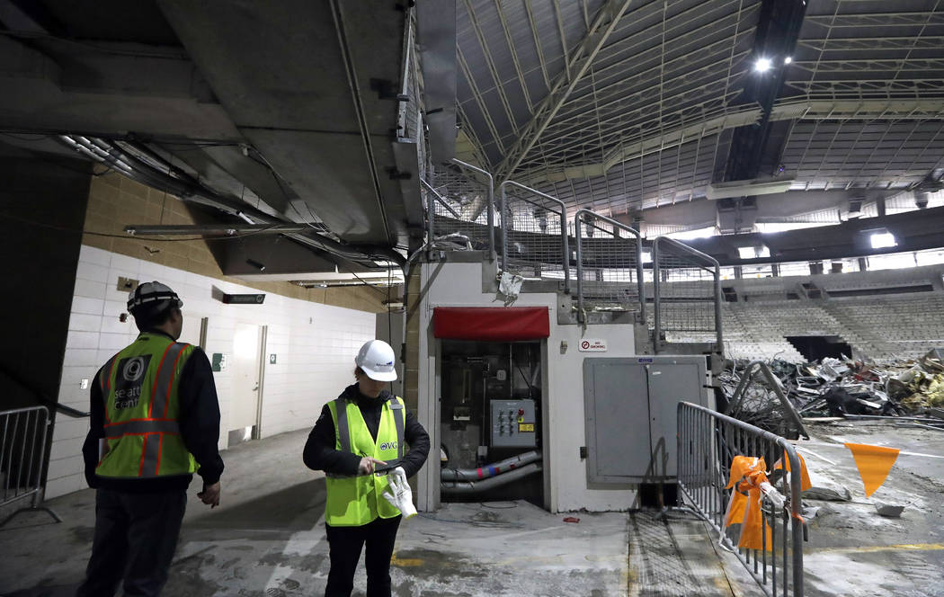 A worker glances down an existing hallway adjacent to the interior of KeyArena in the early sta ...