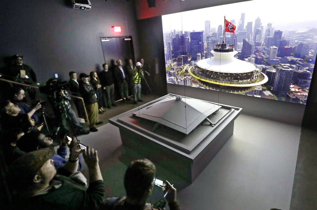 Media members stand near a model of the renovated KeyArena as a video about the plan plays behi ...