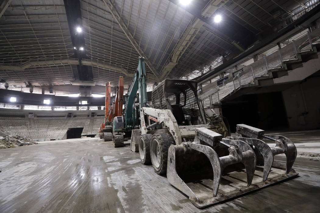 Construction equipment stands on the floor as the interior of the existing roof of KeyArena, th ...