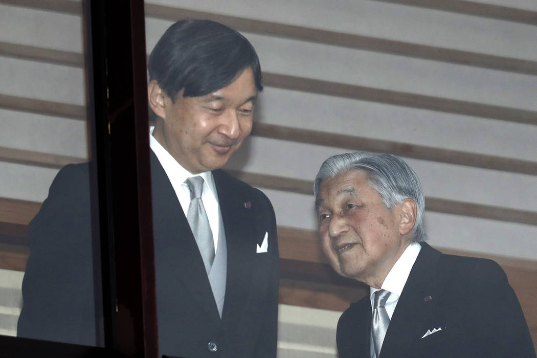 Japan's Emperor Akihito, right, accompanied by Crown Prince Naruhito, walks away after greeting ...