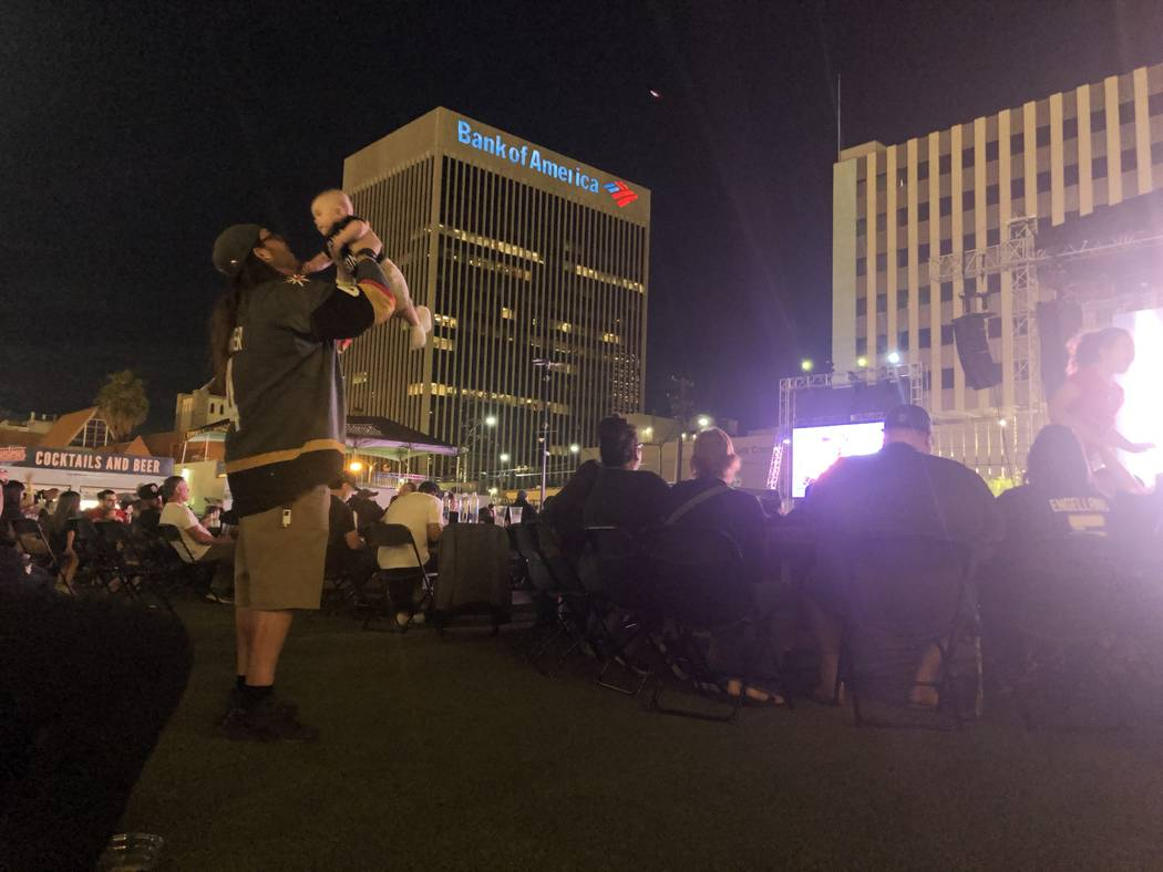 A Las Vegas Golden Knights fan lifts a baby in the air on Thursday, April 18, 2019, at the Down ...