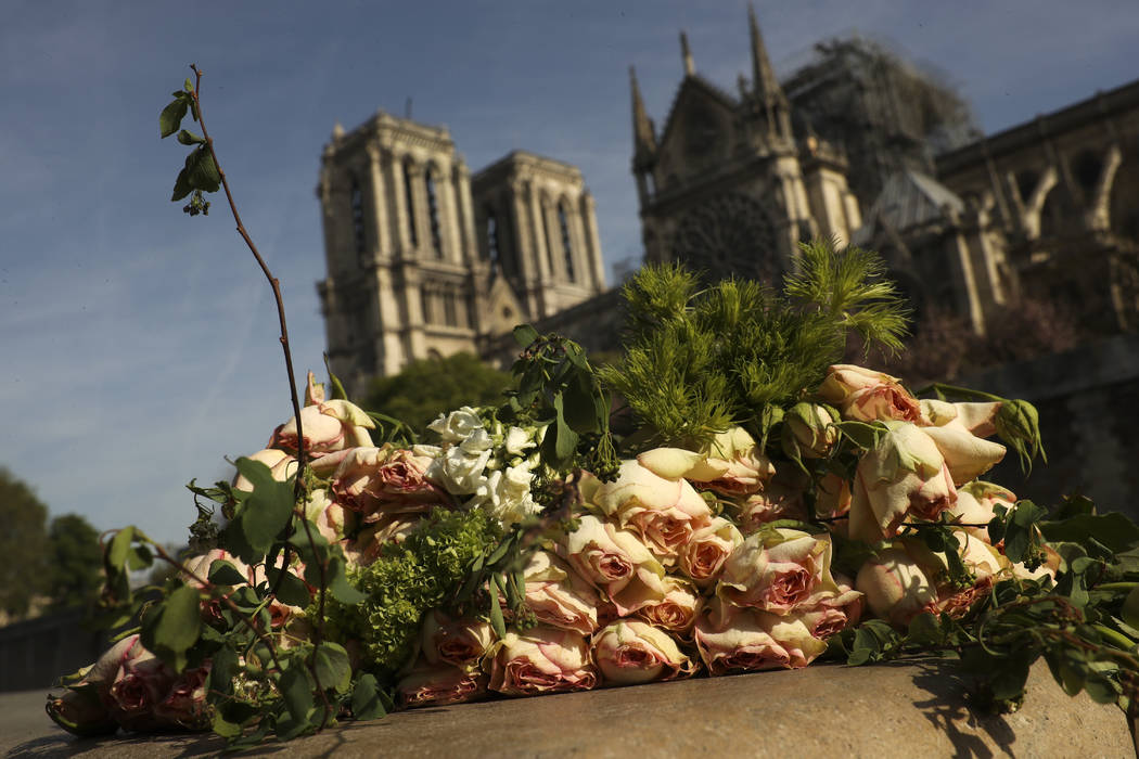 A bunch of flowers lies by the Seine riverside near the Notre Dame cathedral, background, in Pa ...