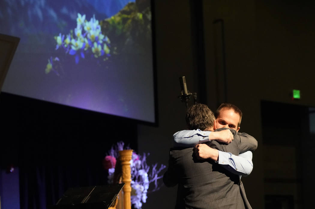 Tom Tonelli, facing camera, a teacher at Columbine High School, hugs former principal Frank DeA ...