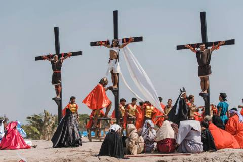 Ruben Enaje, center, dressed as Jesus, is seen nailed on cross for the 33rd year in a row durin ...