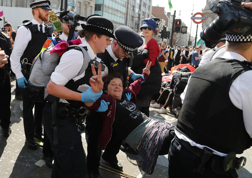 Police arrest protestors at Oxford Circus in London, Friday, April 19, 2019. The environmental ...