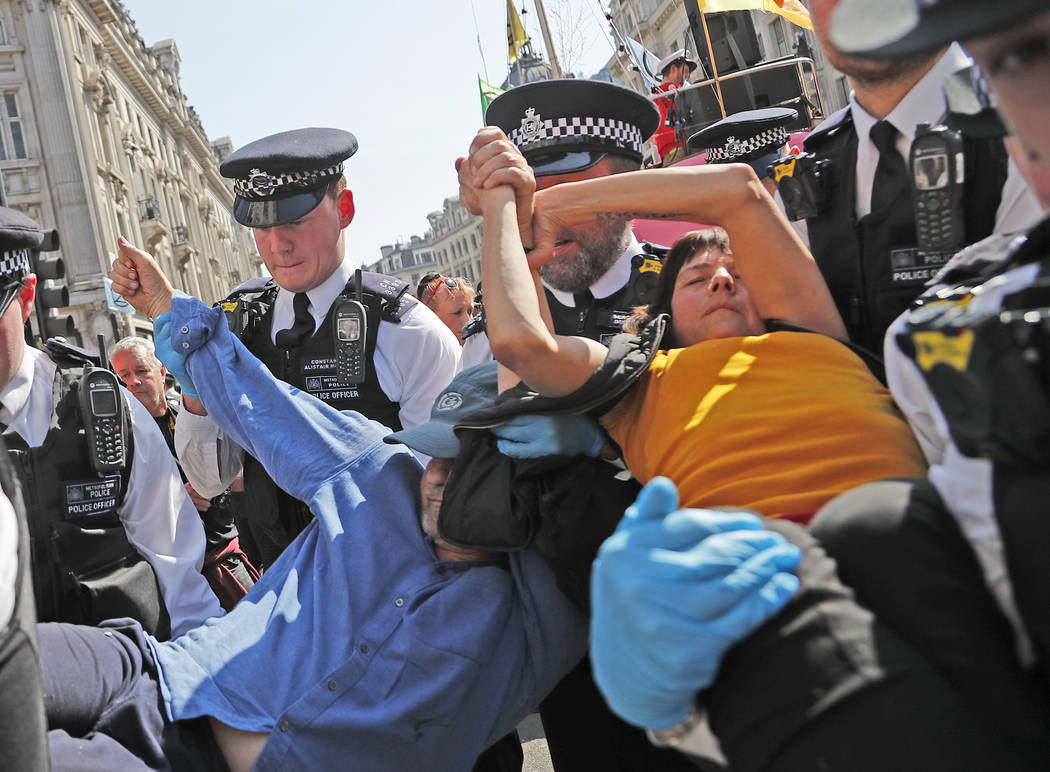 Police arrest a protestor couple who are glued together by their hands, at Oxford Circus in Lon ...