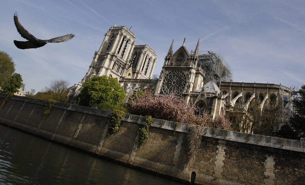 A bird flies past the Notre Dame Cathedral in Paris, Thursday, April 18, 2019. Nearly $1 billio ...
