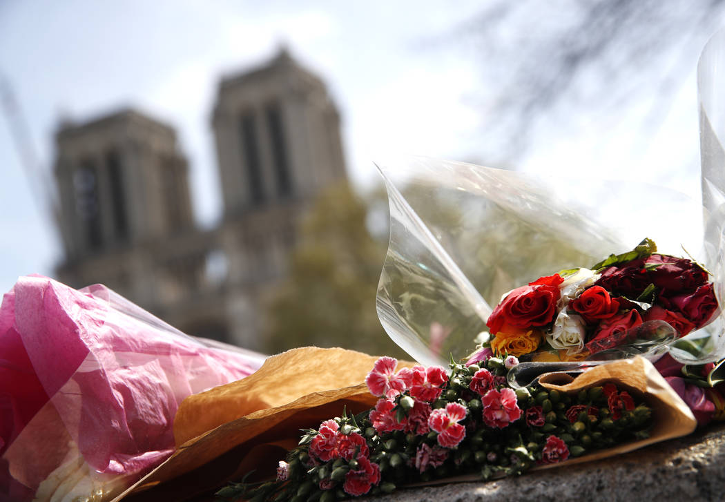 Flowers and tributes are left outside the Notre Dame Cathedral in Paris, Thursday, April 18, 20 ...
