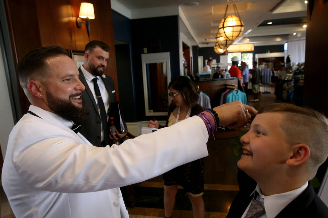 William King fixes his son Enoch's hair before marrying his bride Kimberly at the Revere Golf C ...