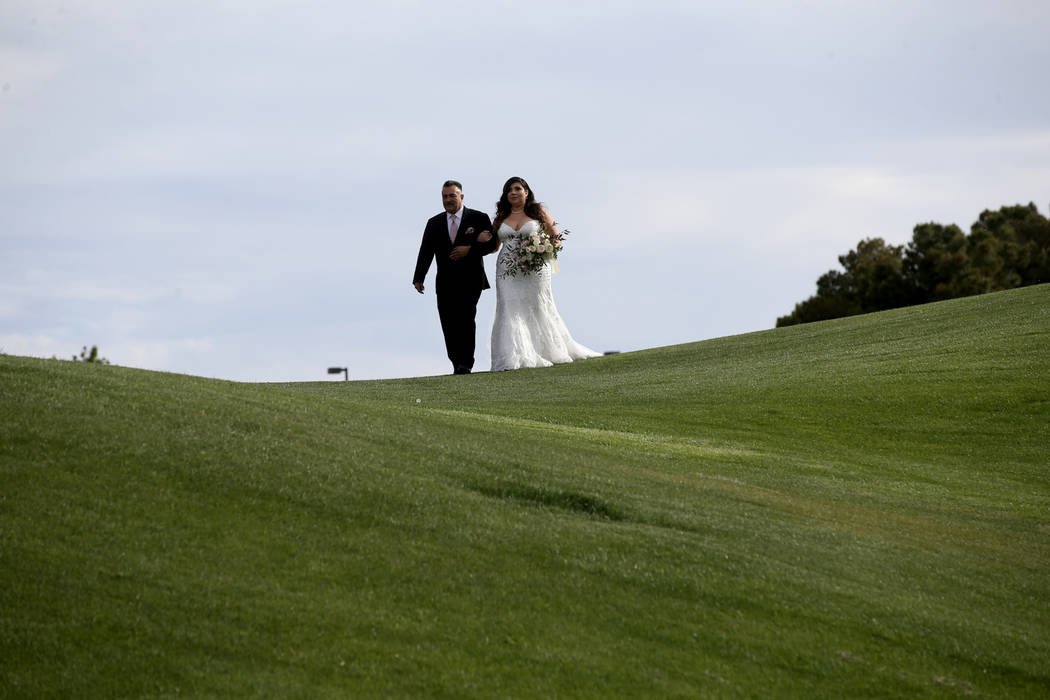 Kimberly King is walked down the isle by her father Manuel Flores at the Revere Golf Club in He ...