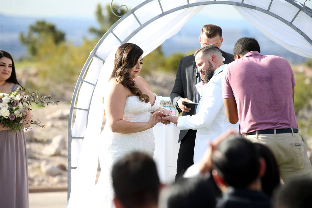 Kimberly and William King exchange rings during their wedding ceremony at the Revere Golf Club ...